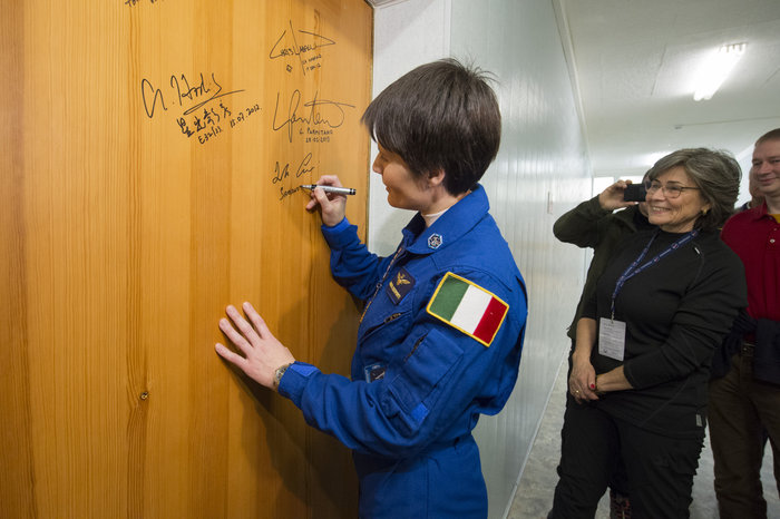 Samantha Cristoforetti performs the traditional door signing at the Cosmonaut Hotel node full image 2